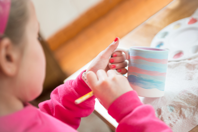 Girl painting beautiful ceramic mug