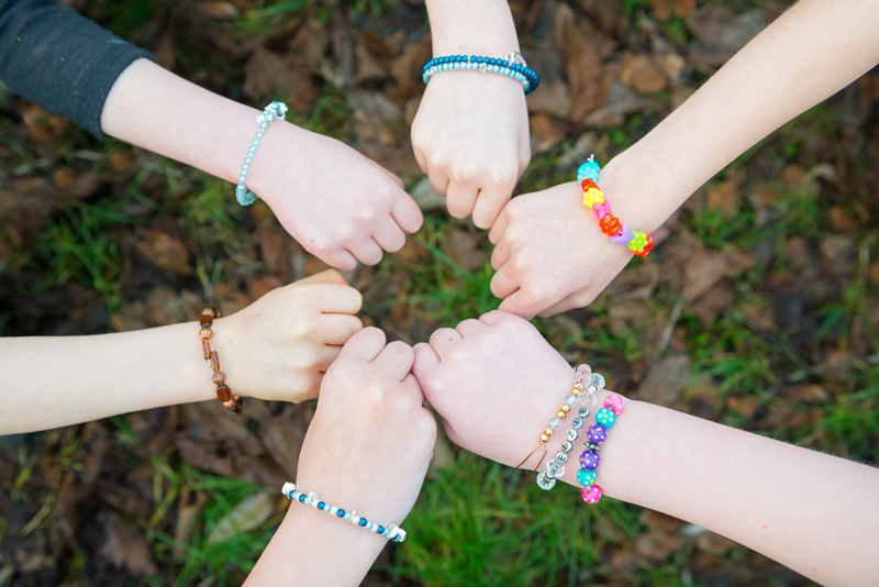 Girls fists all together revealing their hand-made bracelets