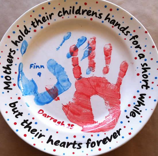 Personalised handprints on handpainted plate.
